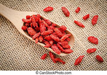 Red dried goji berries in wooden spoon.
