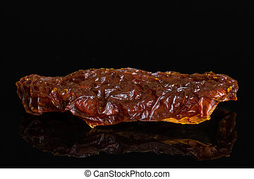 Red dried tomato isolated on black glass