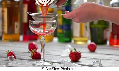 Red drink pours through sieve. Strawberries and ice cubes....