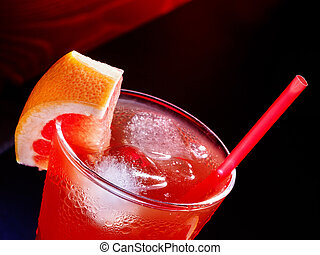Red drink with grapefruit and cube ice on dark background. ...