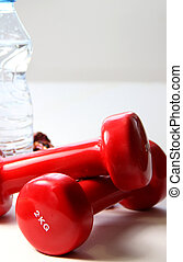 Red dumbbells and bottle of water