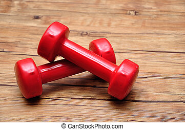Red dumbbells on a wooden background