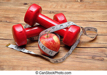 Red dumbbells on a wooden background with a measuring tape and an apple