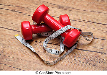 Red dumbbells on a wooden background with a measuring tape