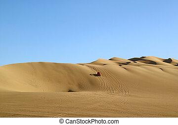 Red dune buggy running on the immense sand dune of Huacachina, Ica region, Peru