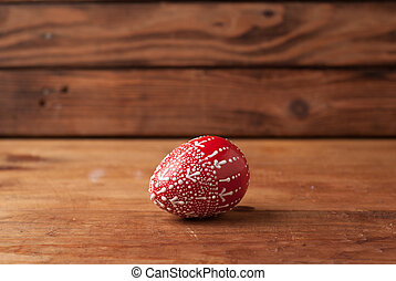Red Easter egg on a wooden table,