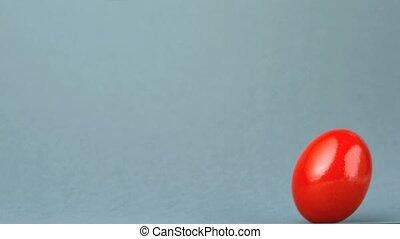 Red egg revolving against grey background in slow motion