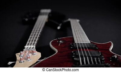 red electric guitar and black bass, lie side by side. Musical equipment