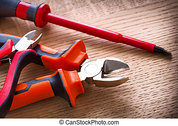 red electric insulated screwdriver and two nippers on wooden...