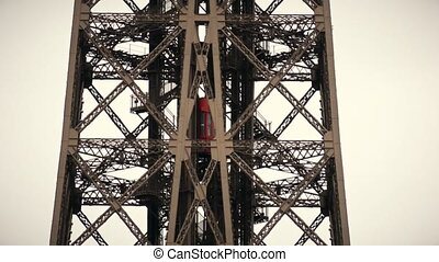 Red elevator moving up to the top of the Eiffel tower in...