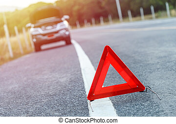 Red emergency stop sign and broken silver SUV car on the road