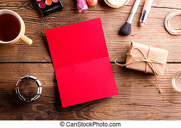 Red empty greeting card on table. Make up products.