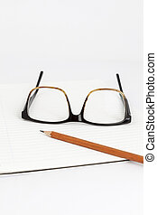 red eyeglasses on a notebook