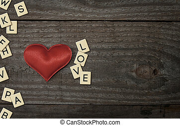 Red fabric heart on wooden table along with the word love