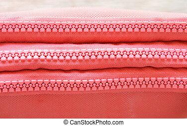 red fabric purse zipper slide opened on wooden board