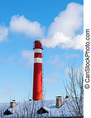 Red factory chimney against blue sky in winter