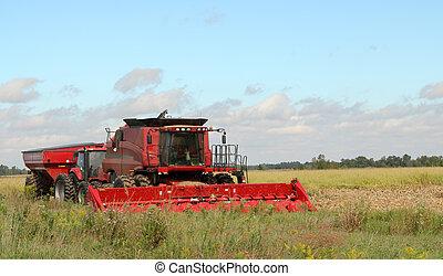 Red farm corn combine and a tractor in a farm field