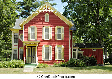 Red Farm House - An old farmhouse in the country with red siding and cream colored shutters and gingerbread trim sits in the shade of huge trees.