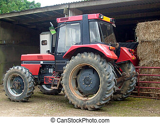 Close up of farm tractor by barn.
