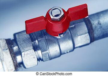 red faucet on metal water pipe closeup