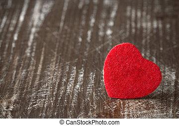 Red felt heart on wooden background.