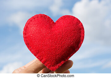Red felt heart shape in the hand on the blue sky with clouds as background. Valentine's card.