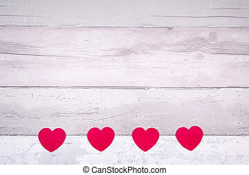 Red felt hearts on a background of old wooden planks resembling an old parquet floor. Concept of valentines day and love in general