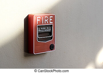 red fire alarm box on cement wall background