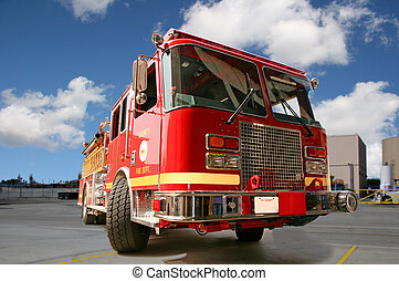 Red Fire Engine - Fire engine on pavement with clouds in the...