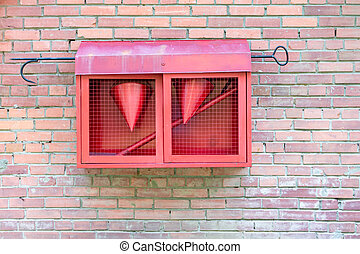 Red fire shield on a brick wall.