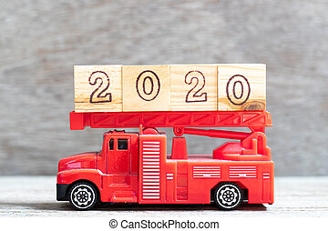 Red fire truck hold letter block in word 2020 on wood background