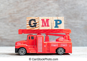 Red fire truck hold letter block in word GMP (Abbreviation ...