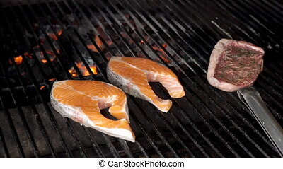 Red fish and meat are cooked on barbecue, cook closes lid of...