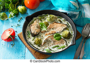 Red fish and vegetables baked (brussels sprouts, green beans) in cream sauce in a frying pan in a rustic style.