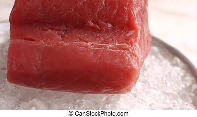 Red fish meat lying on ice.