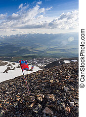 red flag flying in the background of the mountains