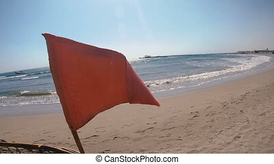 Red flag hanging on the beach
