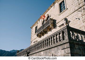 Red flag of Montenegro on a building with a large balcony among the mountains against a blue sky.