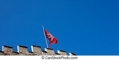 red flag of the fortress against the blue sky