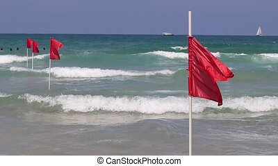 Red flag on sand beach for warning of dangerous of swimming...