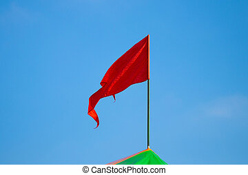 Red flag waving on blue sky background