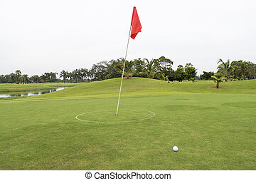 Red flag with Golfball on grass in golf course of the green