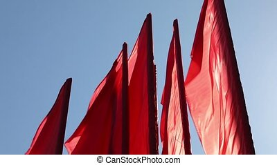 Red flags against the blue sky - Red flags waving in the...