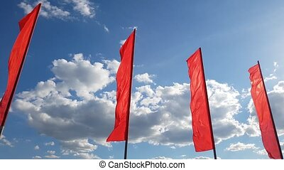 Red flags swaying in wind against the blue sky.