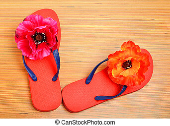 Red flip-flops, slippers with flowers on the wood