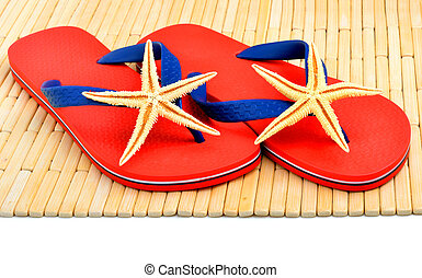 Red flip-flops, slippers with starfish on the wooden background