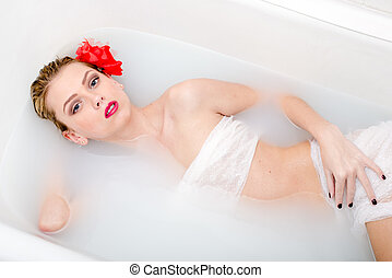 red flower spa: portrait of attractive happy smiling blond girl beautiful young woman relaxing taking bath and looking at camera image