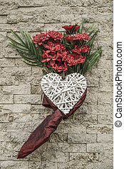 red flowers hanged on a wall with white heart