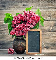 Red flowers in vase on wooden background. Blackboard