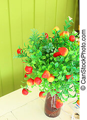 red flowers vase on wood green background